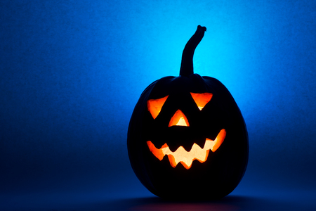 Photo for Halloween pumpkin, silhouette of funny face on blue background. - Royalty Free Image