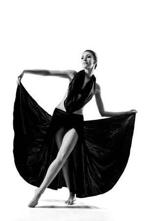 Photo for A beautiful athletic girl in a black dress is dancing - Royalty Free Image
