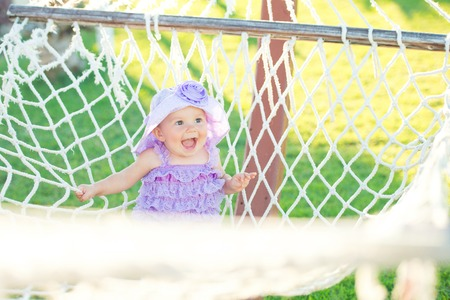 Portrait of happy girl on vacation. Against a background of hammocks, a little girl is sitting in a purple plait. little girl laughing, close-up portrait
