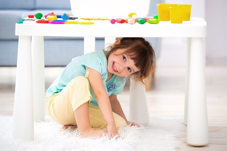 Photo pour Little cute girl crawled under the table. The kid smiles, plays hide and seek. - image libre de droit