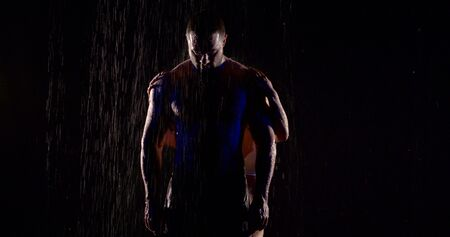 Foto de half naked muscular man is standing under rain in darkness, female hands are stroking his body from back - Imagen libre de derechos