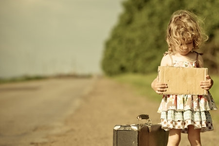 Lonely girl with suitcase standing about road and holding paper with copyspace in hands