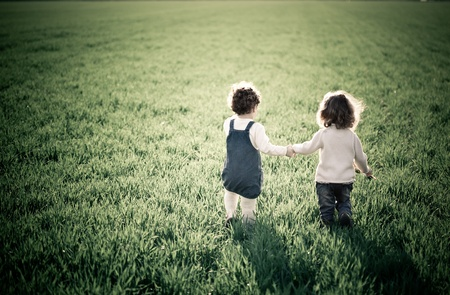 Photo for Two children going in spring green field - Royalty Free Image
