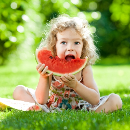 Photo for Happy child sitting on green grass and eating watermelon outdoors in spring park against natural sunny blurred background - Royalty Free Image