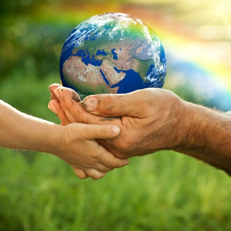 Photo pour Hands of senior man and baby holding Earth against a rainbow in spring  Ecology concept - image libre de droit