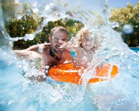 Photo pour Happy family playing in blue water of swimming pool on a tropical resort at the sea. Focus on children`s hand and splash, shot was taken with waterproof box - image libre de droit