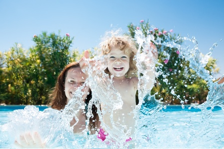 Happy family playing in blue water of swimming pool on a tropical resort at the sea  Summer vacations concept