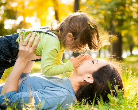 Happy family lying on grass in autumn park