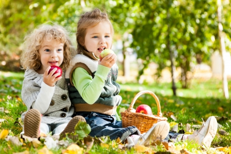 Photo for Children eating apples in autumn park  Family picnic - Royalty Free Image