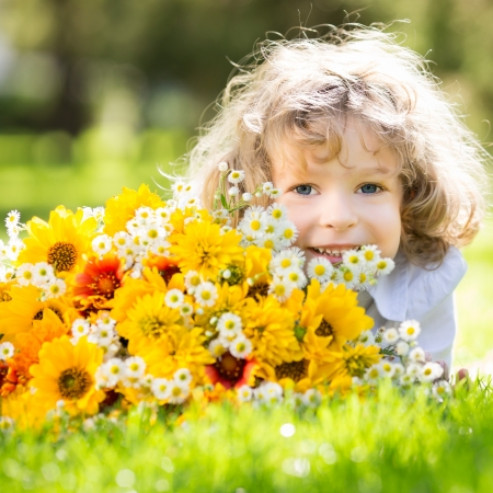 Foto de Happy smiling child with big bouquet of spring flowers lying on green grass - Imagen libre de derechos