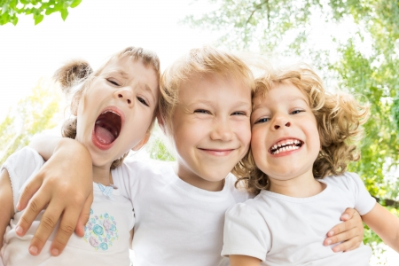 Photo for Low angle view portrait of happy children making silly faces outdoors in spring park. Fisheye shot - Royalty Free Image
