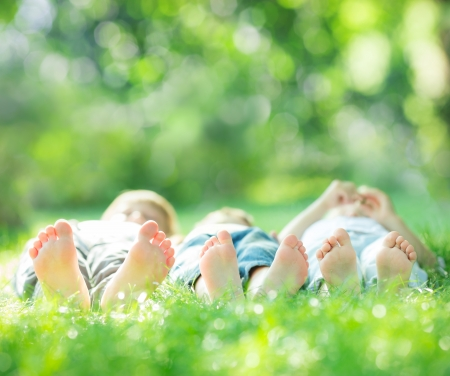 Happy family lying on green grass in spring park. Healthy lifestyle concept. Farmland vacations