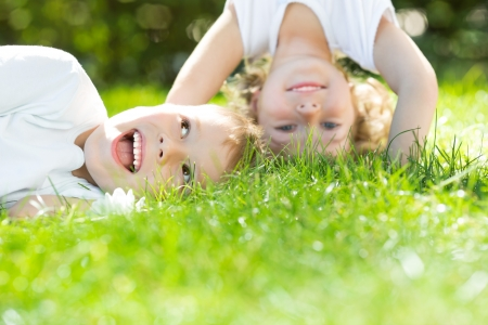 Photo pour Happy children standing upside down on green grass in spring park  Healthy lifestyles concept  - image libre de droit