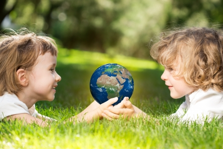 Children s holding world in hands against green spring background  Earth day concept
