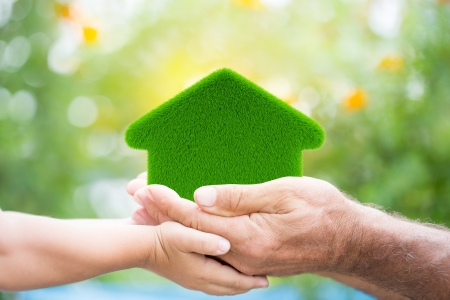 Family holding grass house in hands against green spring background  Environment protection concept