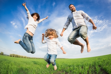 Happy active family jumping in green field against blue sky