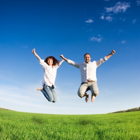 Happy couple jumping in green field against blue sky  Summer vacation concept