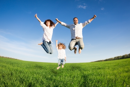 Foto de Happy family jumping in green field against blue sky  Summer vacation concept - Imagen libre de derechos