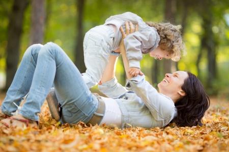 Foto de Happy family having fun outdoors in autumn park against blurred leaves background - Imagen libre de derechos