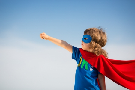 Photo for Superhero kid against blue sky background - Royalty Free Image