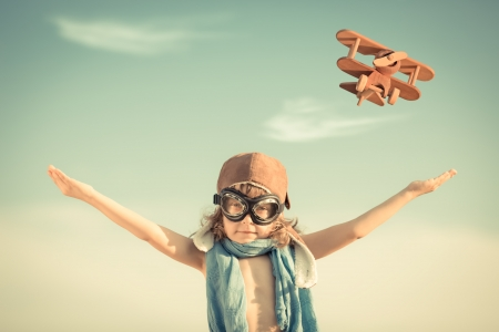 Photo pour Happy kid playing with toy airplane against blue summer sky background - image libre de droit