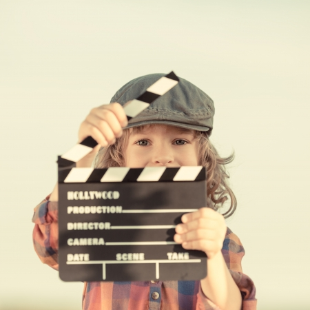 Photo for Kid holding clapper board in hands - Royalty Free Image