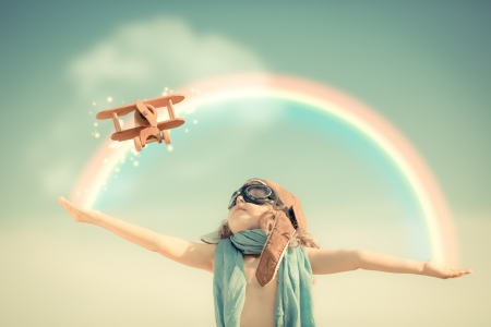 Foto de Happy kid playing with toy airplane against summer sky background - Imagen libre de derechos