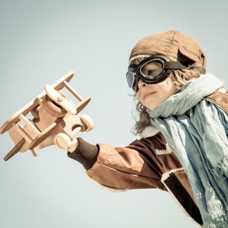 Foto de Happy kid playing with wooden toy airplane in autumn - Imagen libre de derechos