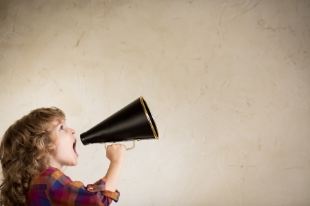 Photo pour Kid shouting through vintage megaphone. Communication concept. - image libre de droit