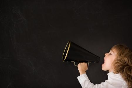 Photo for Kid shouting through vintage megaphone against blackboard - Royalty Free Image