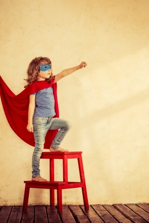 Photo pour Full length portrait of superhero kid against grunge wall background - image libre de droit