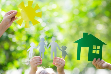 Foto de Ecology house and family in hands against spring green background - Imagen libre de derechos