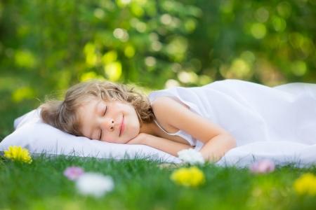 Photo pour Happy kid sleeping on green grass outdoors in spring garden - image libre de droit