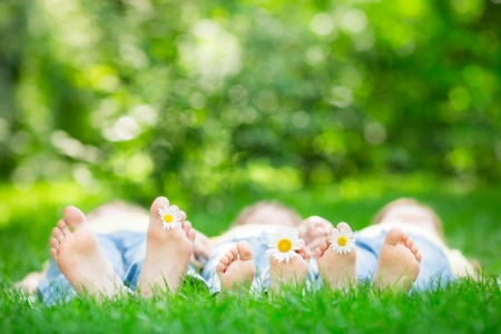 Foto de Family lying on grass outdoors in spring park - Imagen libre de derechos