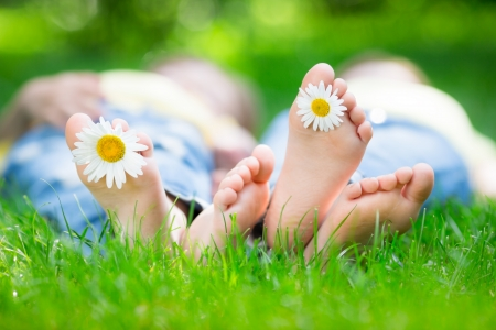 Foto de Couple lying on grass outdoors in spring park - Imagen libre de derechos