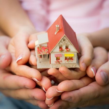 Foto de Family holding little house in hands. Real estate concept - Imagen libre de derechos