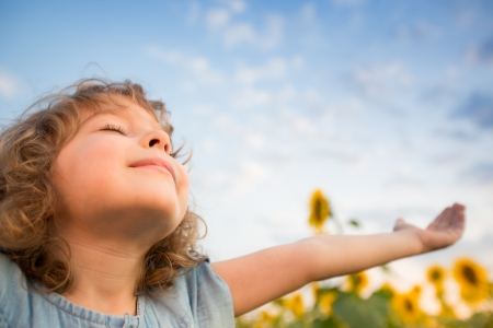 Photo pour Happy child outdoors in spring sunflower field - image libre de droit