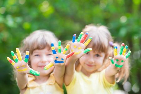 Photo pour Children with smiley hands against green spring  - image libre de droit