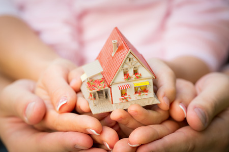 Photo for Family holding house in hands. Real estate concept - Royalty Free Image