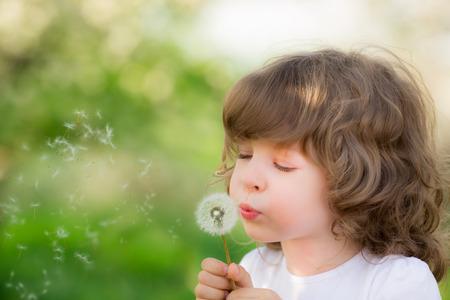 Foto de Happy child blowing dandelion outdoors in spring park - Imagen libre de derechos