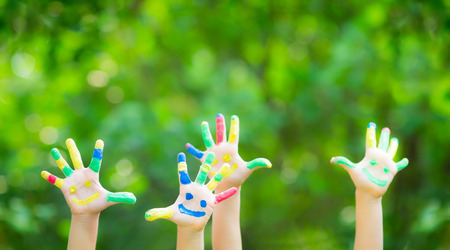 Photo for Happy child with smiley on hands against green spring background - Royalty Free Image