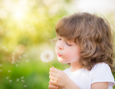 Foto de Happy child blowing dandelion outdoors in spring park - Imagen libre de derechos