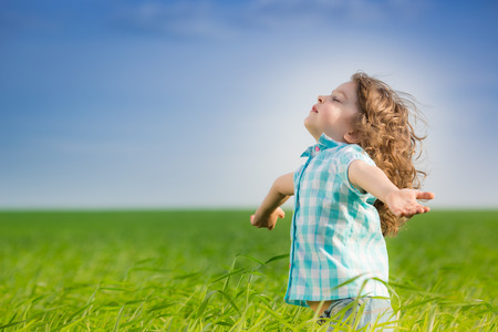 Foto de Happy kid with raised arms in green spring field against blue sky. Freedom and happiness concept - Imagen libre de derechos