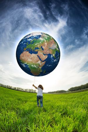 Foto de Child holding Earth in hand against blue sky and spring green field.   - Imagen libre de derechos