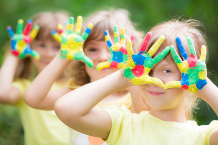 Foto de Happy child with painted hands against green spring background - Imagen libre de derechos
