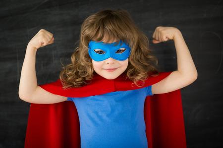 Photo pour Superhero kid against school blackboard - image libre de droit