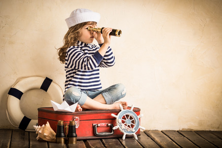 Photo pour Happy kid playing with toy sailing boat indoors. Travel and adventure concept - image libre de droit