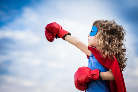 Photo pour Superhero kid against summer sky background. Girl power and feminism concept - image libre de droit
