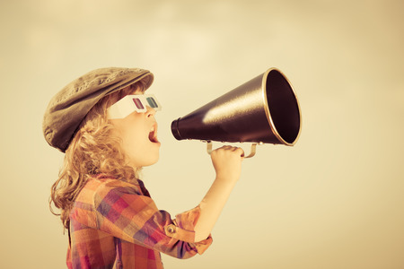 Photo pour Child shouting through vintage megaphone - image libre de droit