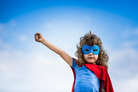 Foto de Superhero child against blue sky background - Imagen libre de derechos